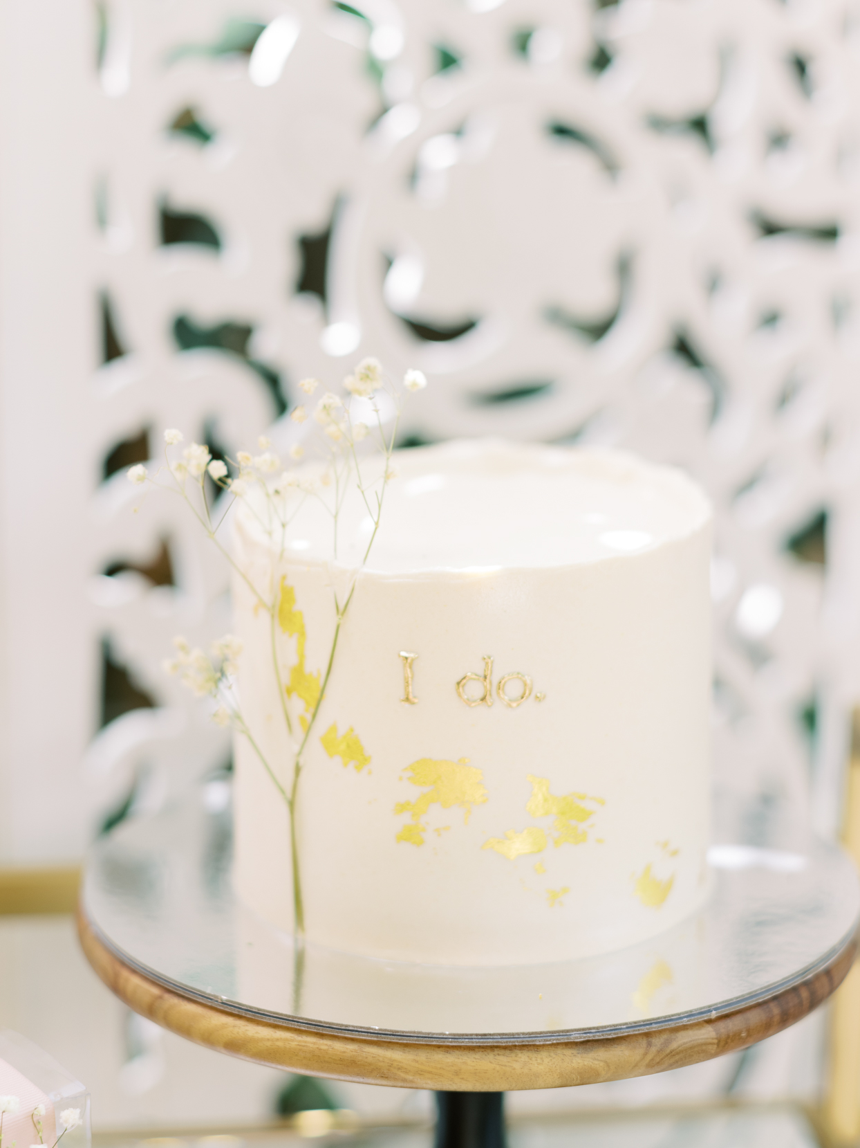 """white wedding cake with """"i do"""" in gold"""