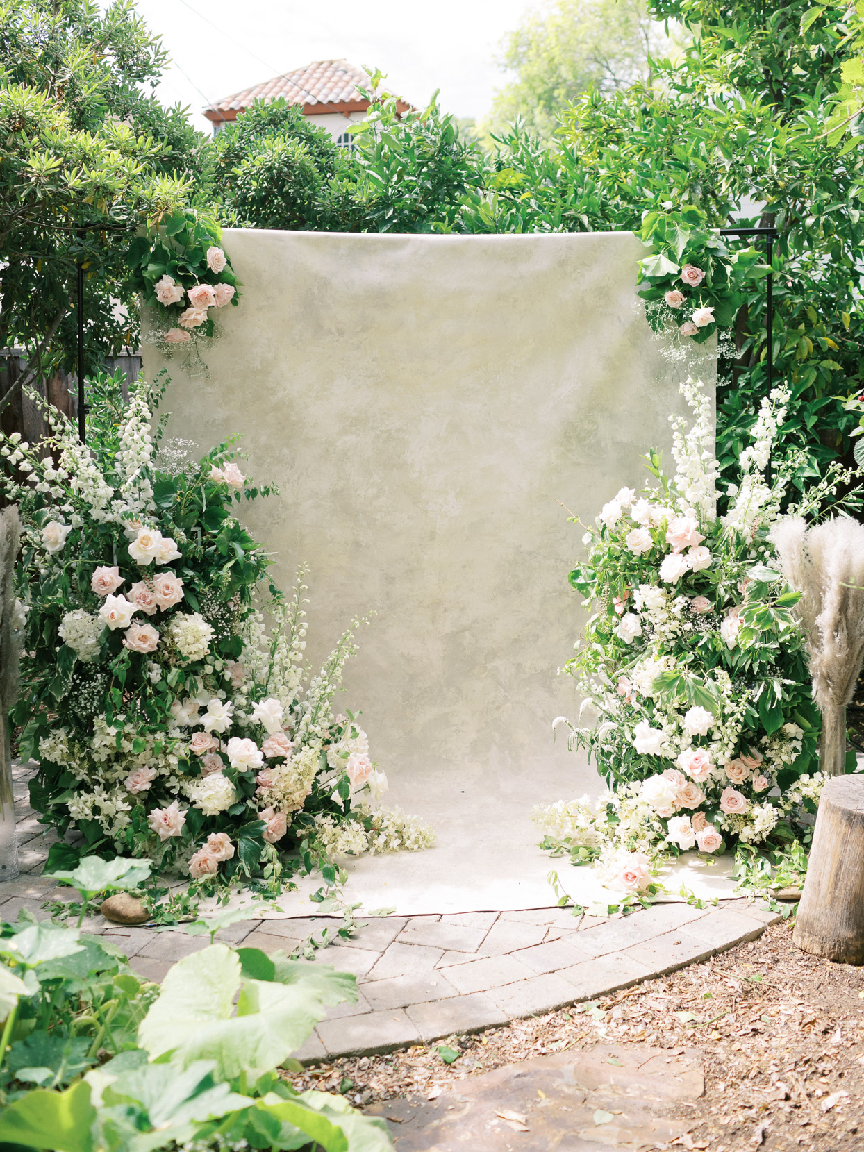wedding garden ceremony with beige backdrop and florals