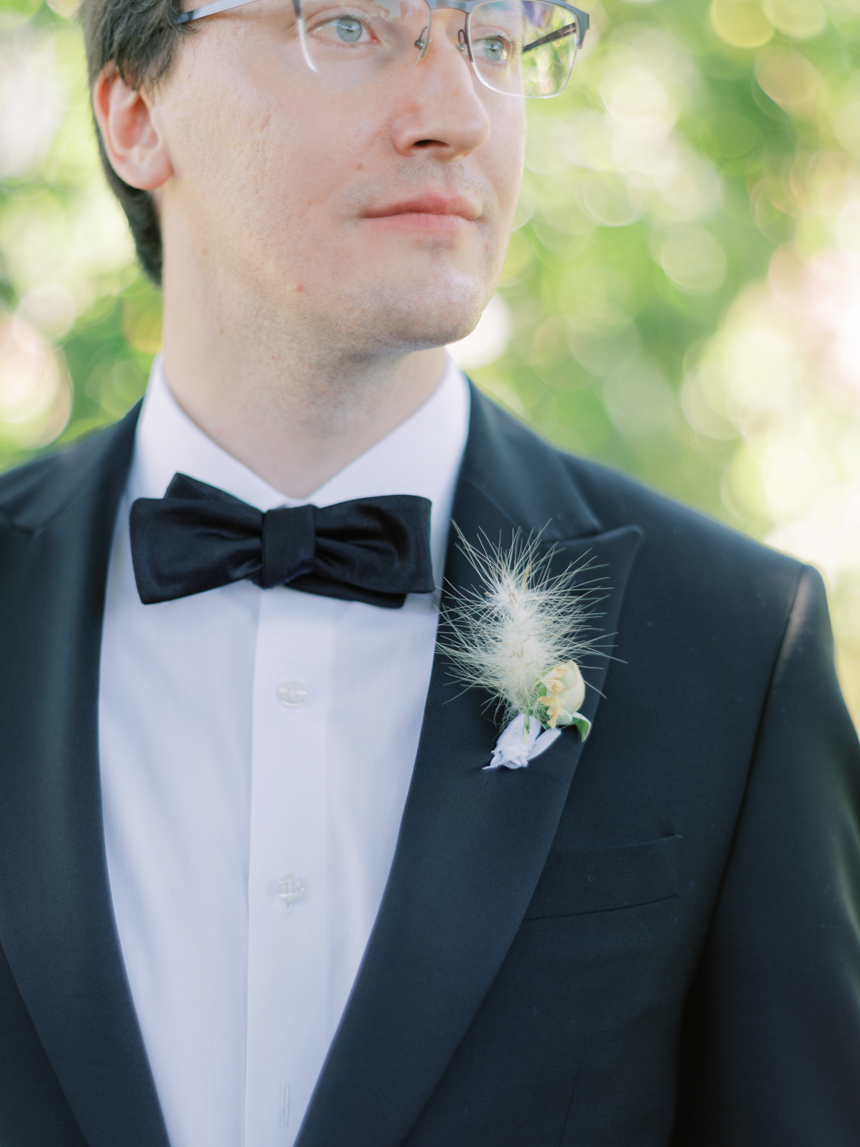 close up of groom's feather and flower boutonniere