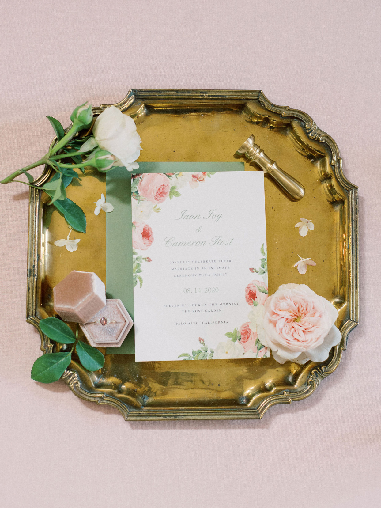 pink and white wedding invitations on gold tray