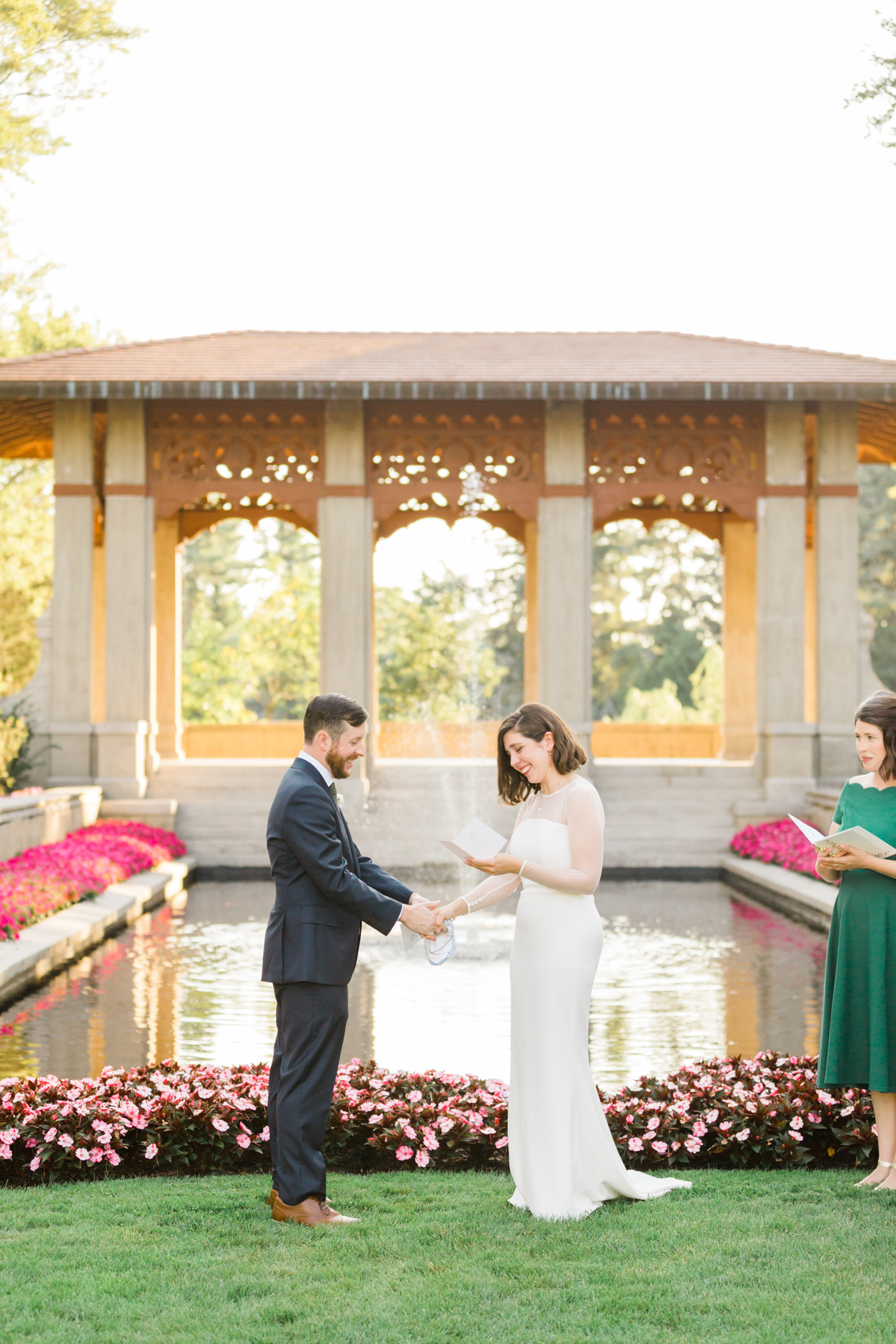 bride and groom exchanging vows in front of garden pond