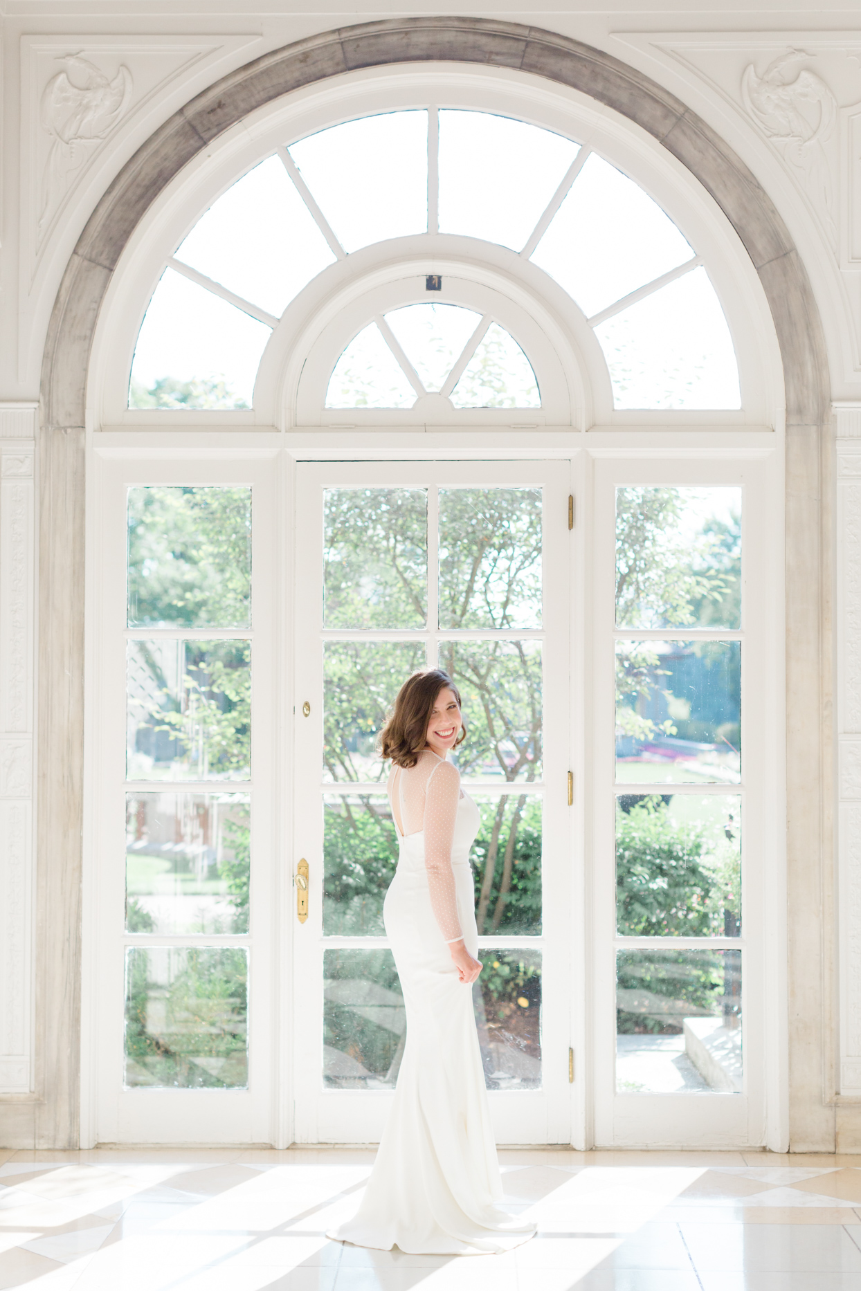 bride smiling in mermaid wedding dress in front of windows