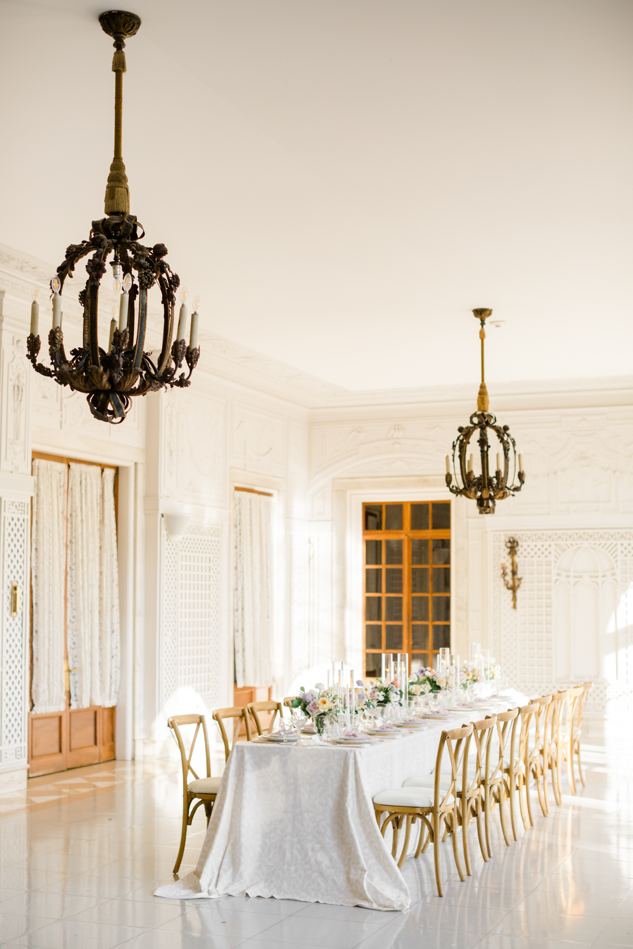 reception long table in white and gold room with antique chandeliers
