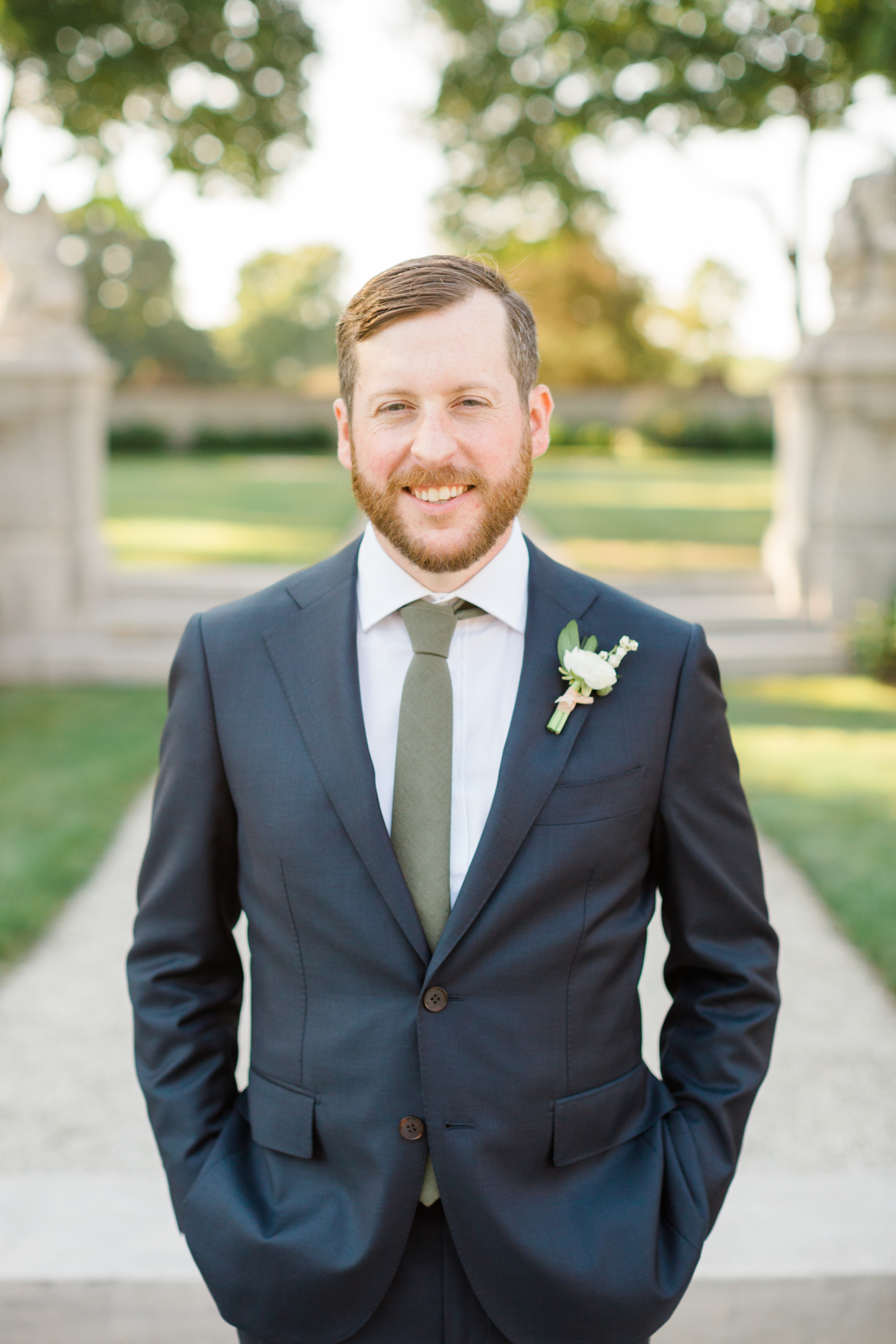 groom in wedding suit with green tie