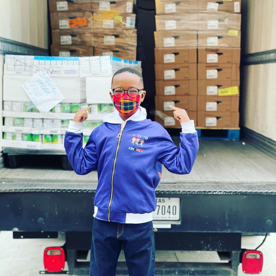 orion jean posing in front of truck delivering meals for his race to 100k meals campaign