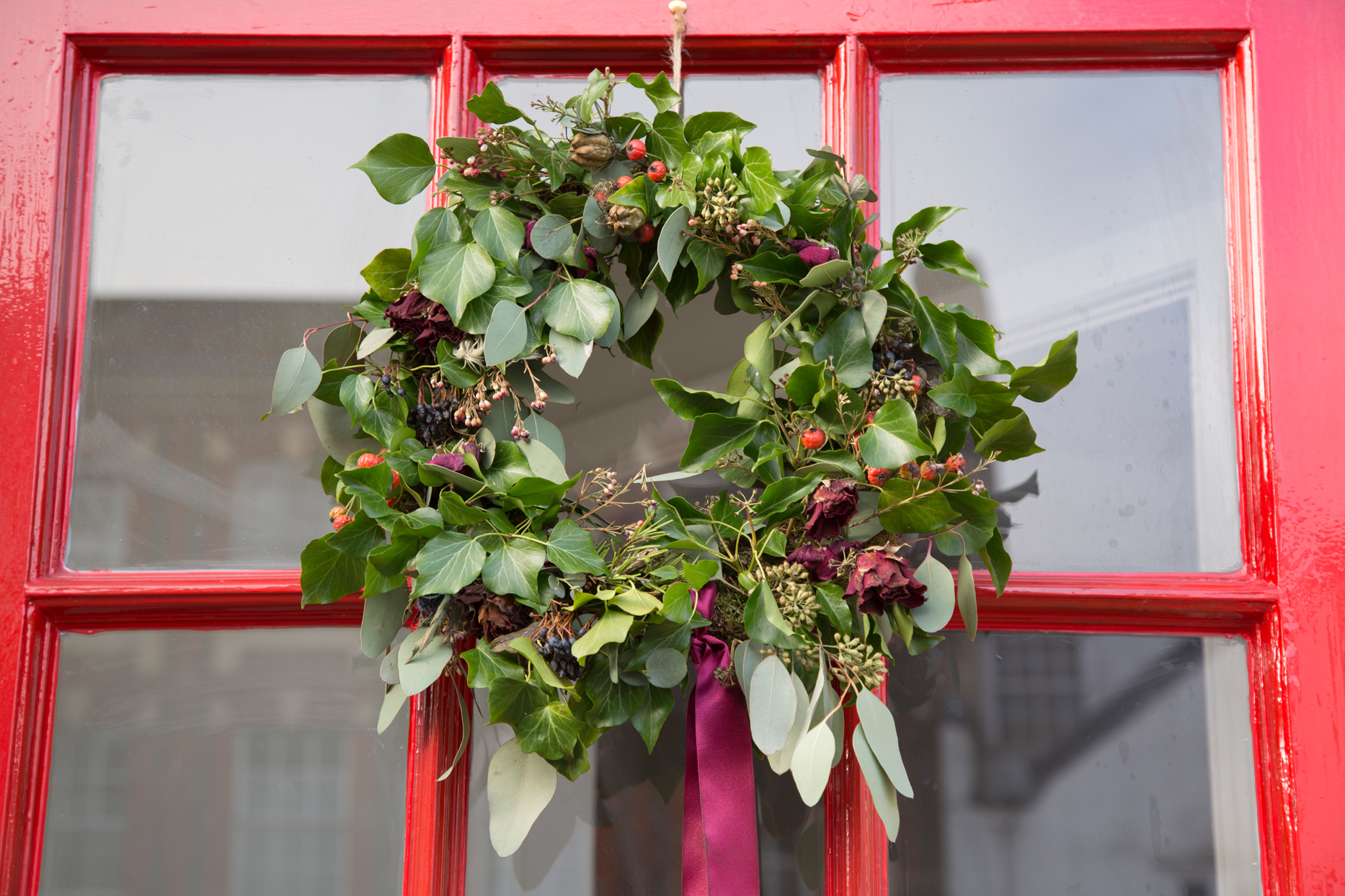 green wreath with berries and floral accents hanging on red door