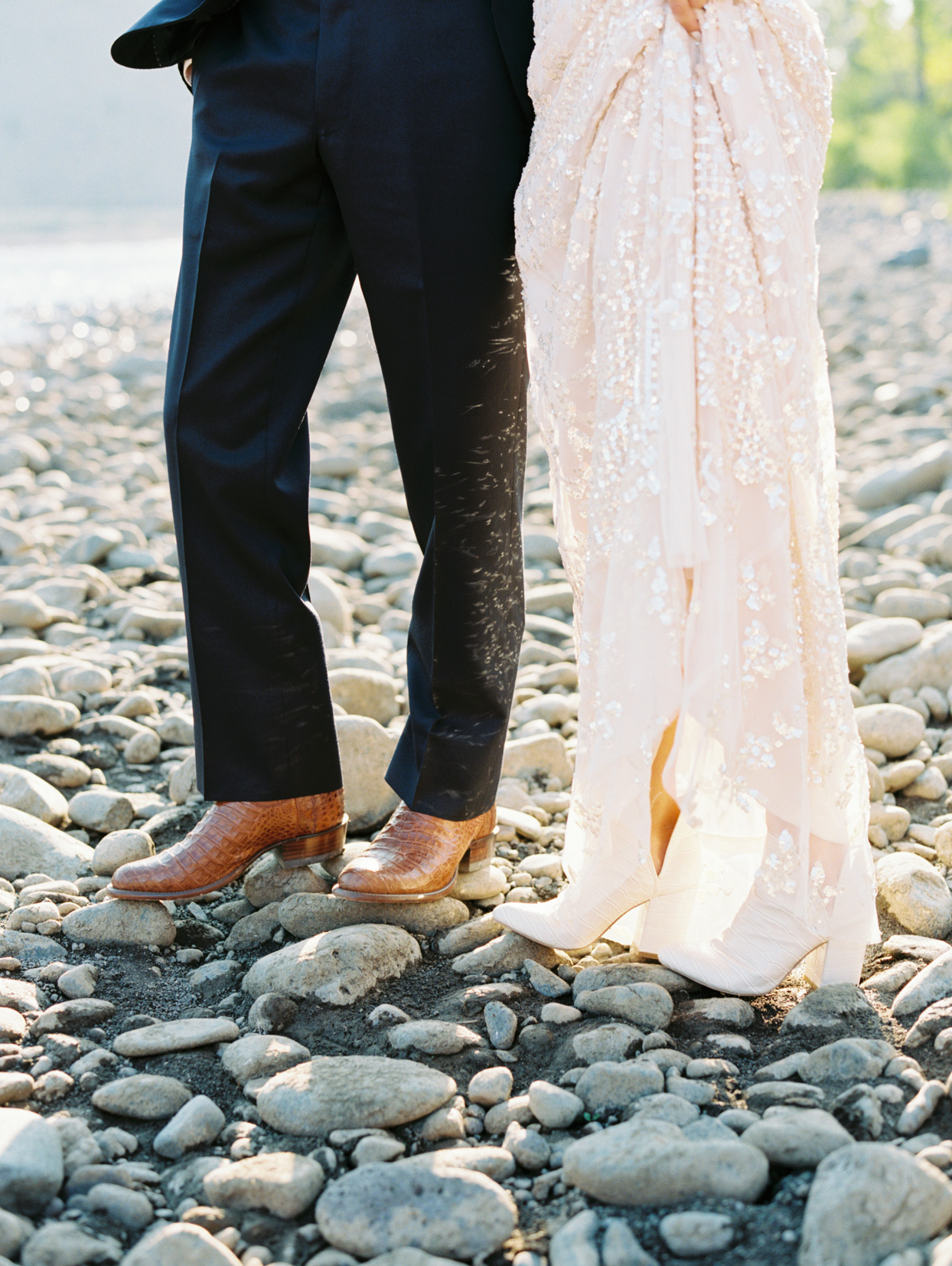 bride and groom where leather boots standing on the rocks