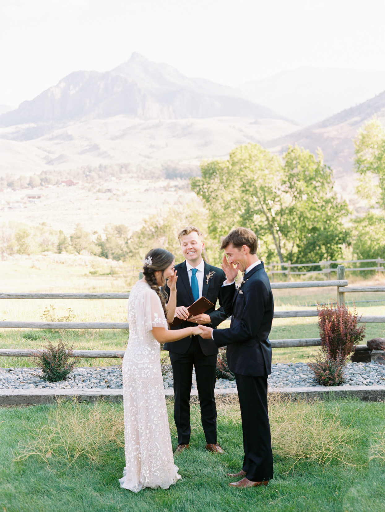 couple crying during wedding ceremony with mountain backdrop