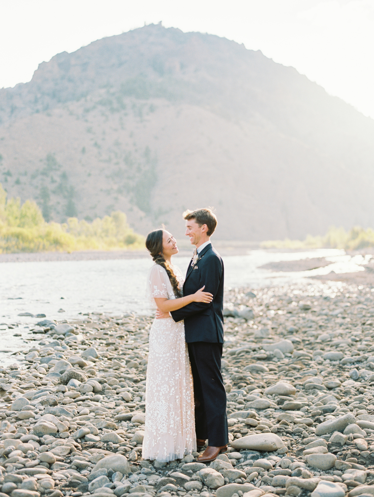wedding couple portrait by water and mountains