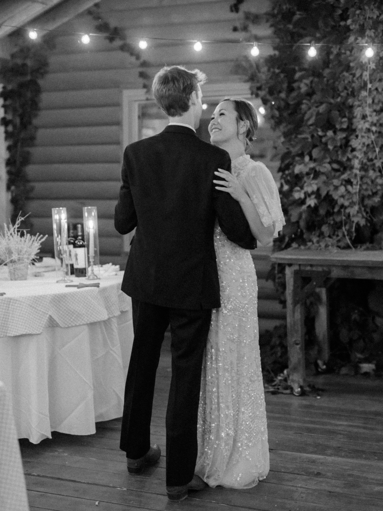 couple dancing under string lights at reception