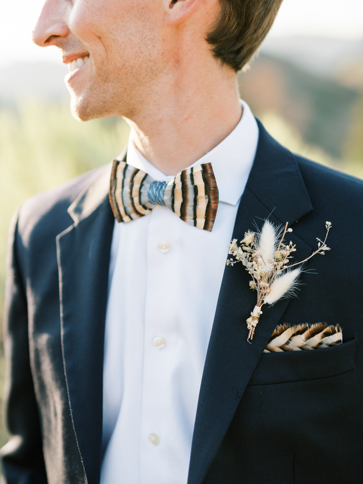 groom in black suit with feather bowtie and boutonniere