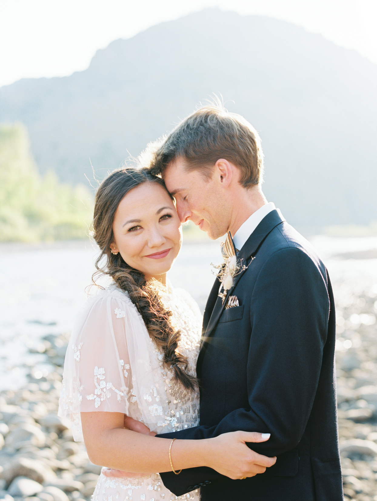 couple hugging for portrait with mountain backdrop