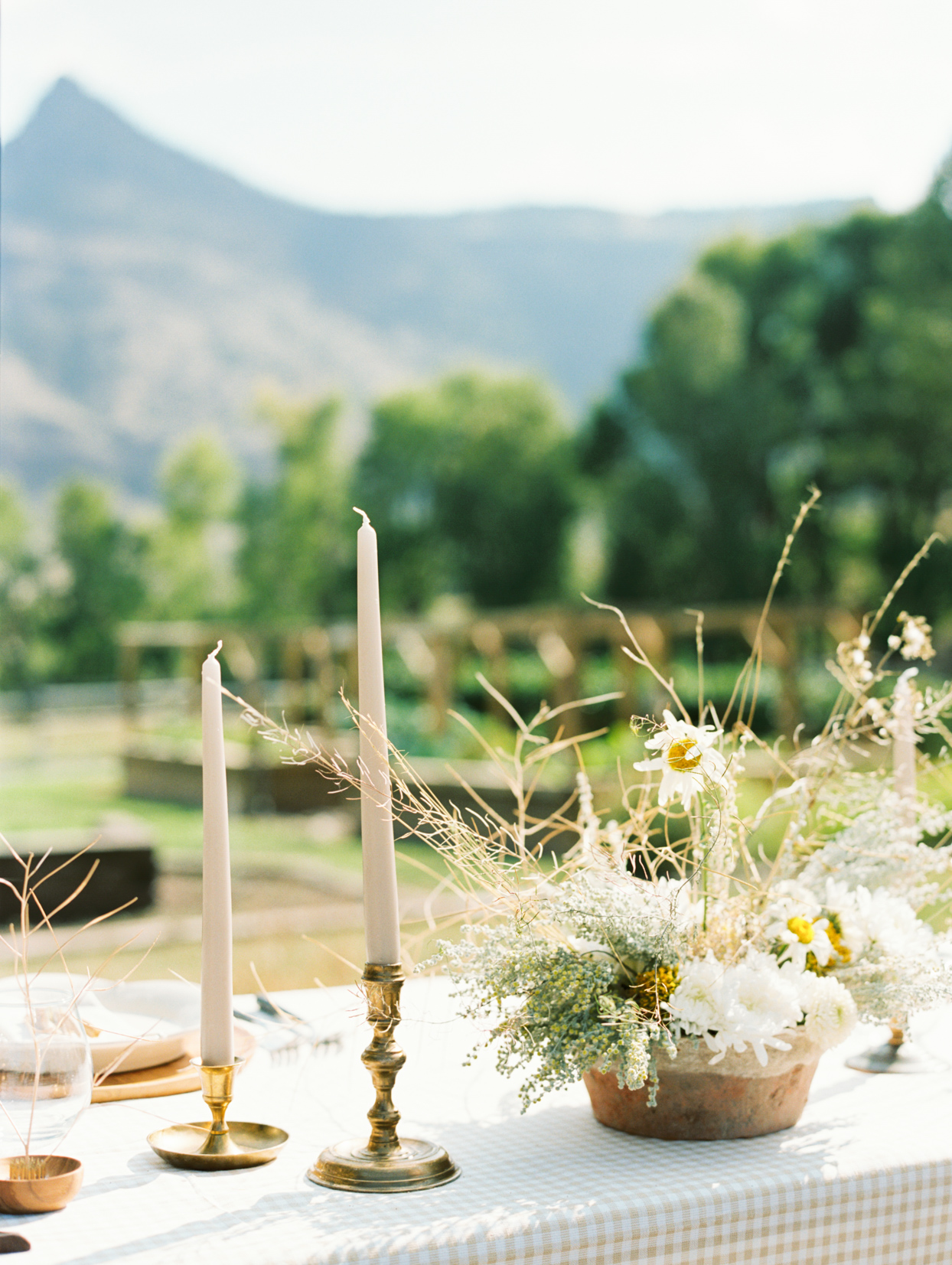 rustic table setting with plaid cloth, candles, wild bouquet