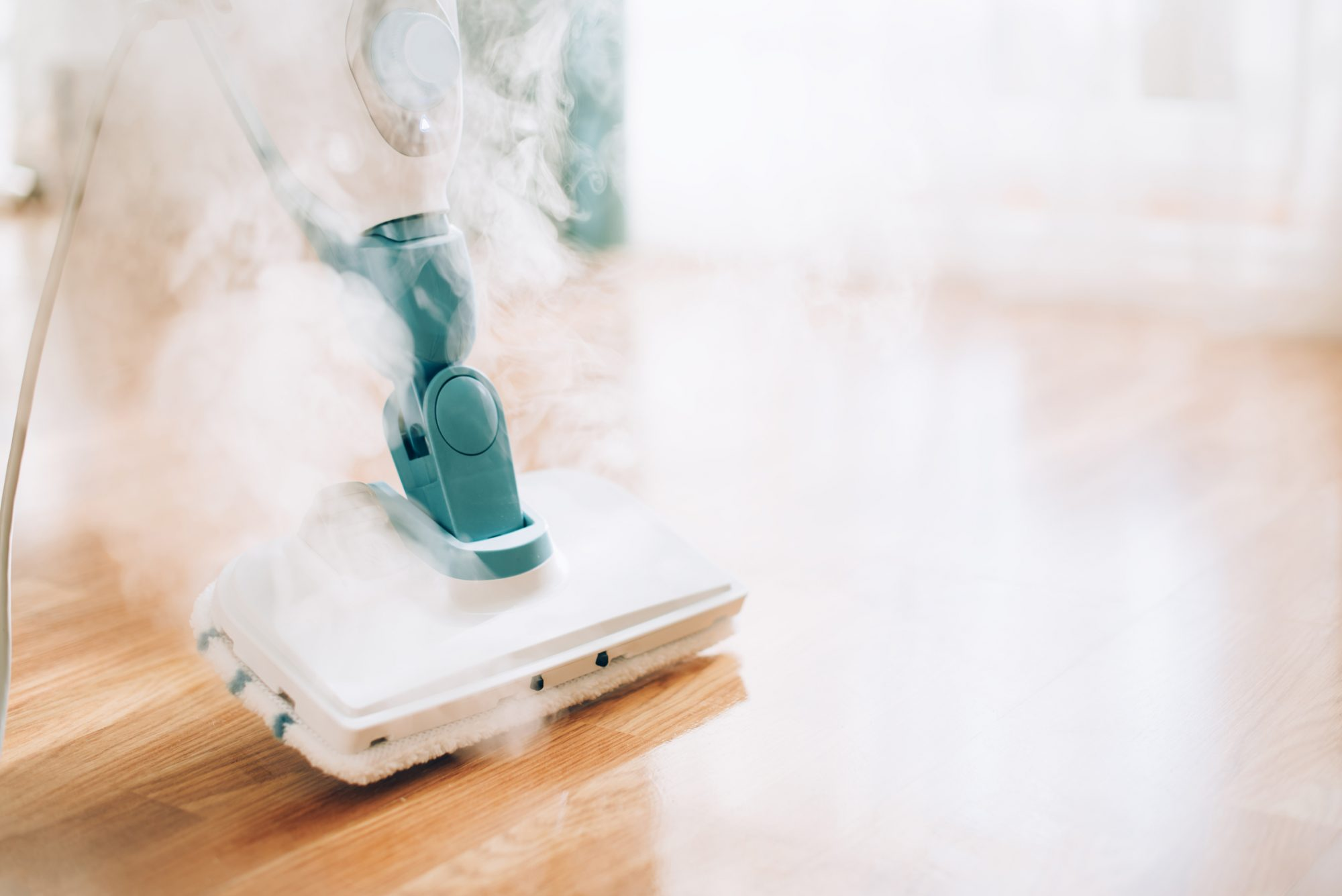 white and green steam mop being used on the wood floor