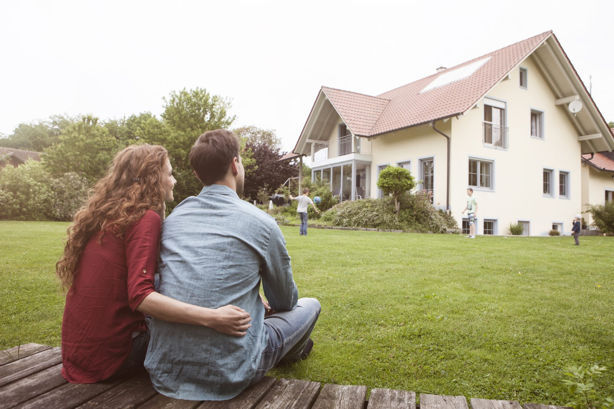 Couple sitting in garden looking at their house