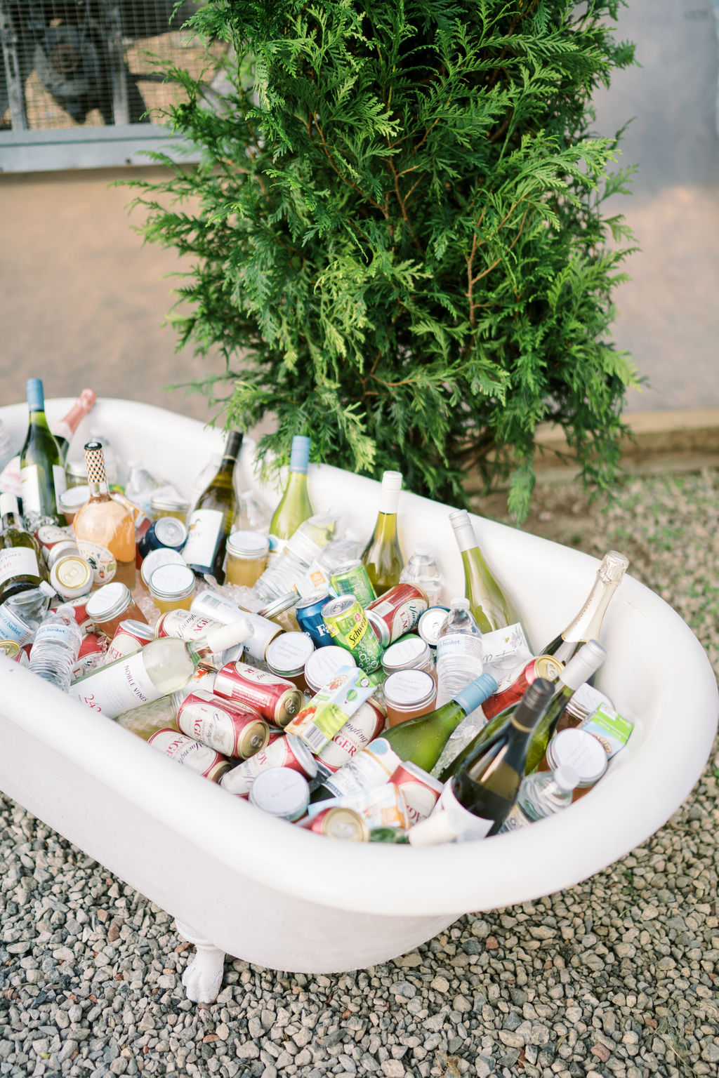 white clawfoot tub filled with assorted alcoholic beverages