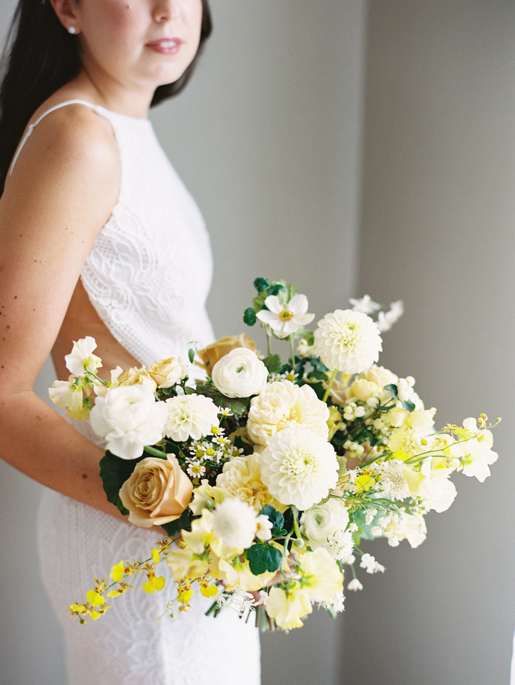 bride holding white and yellow floral wedding bouquet
