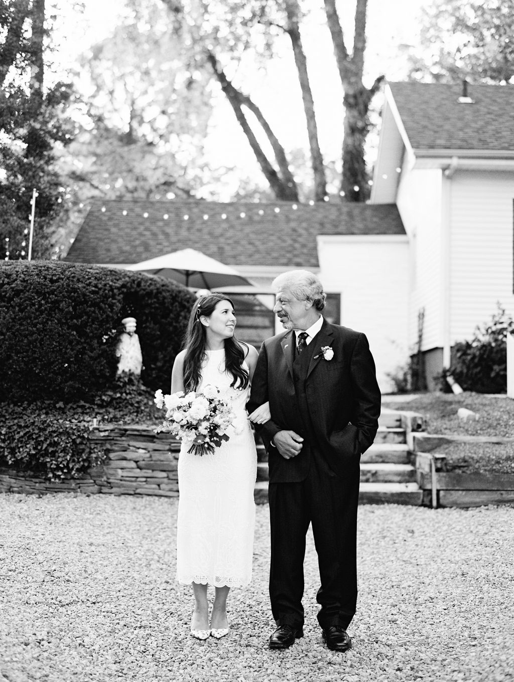 bride and dad standing smiling at each other with arms linked