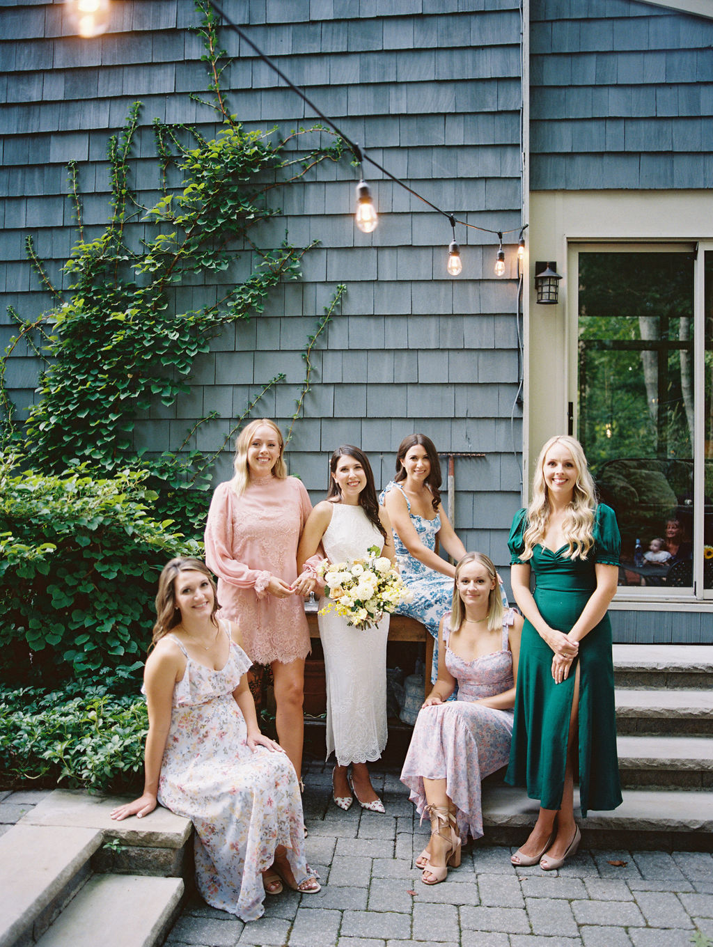 bride smiling with five bridesmaids wearing various style and colored dresses