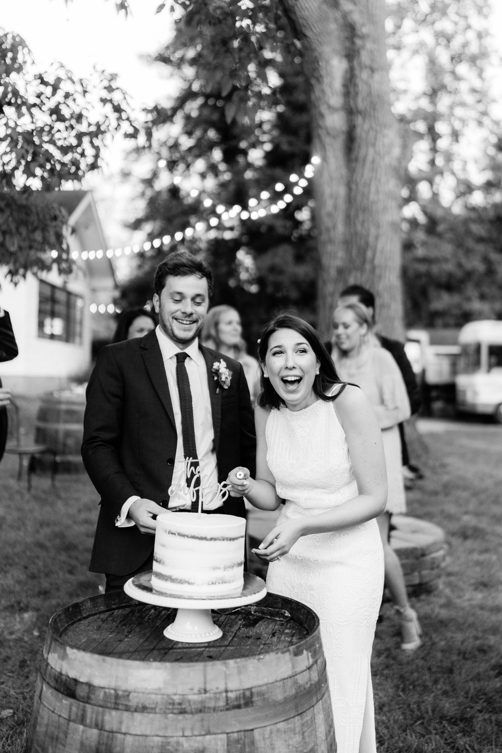 bride and groom smiling during cake cutting outside