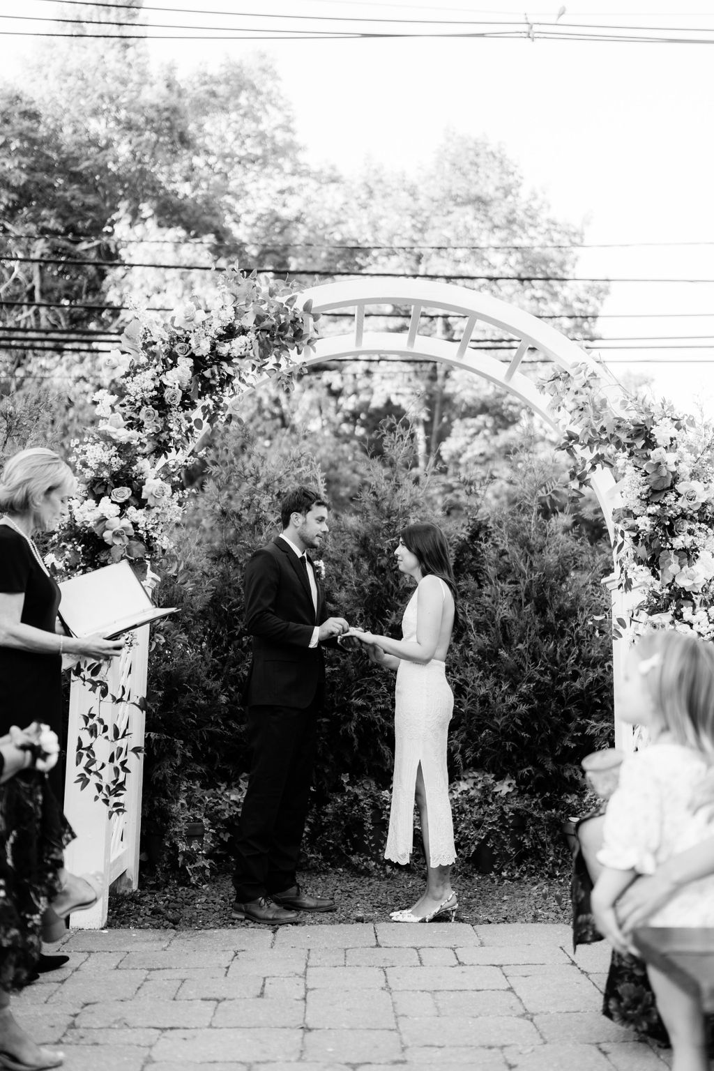 bride and groom standing under floral covered arch during wedding ceremony