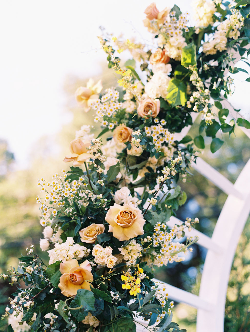 white and yellow floral and greenery covered wedding ceremony arch
