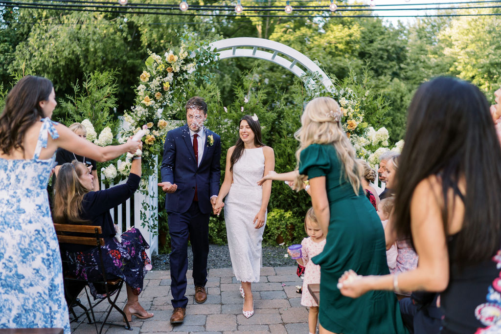 guests tossing rice at bride and groom during wedding recessional outside