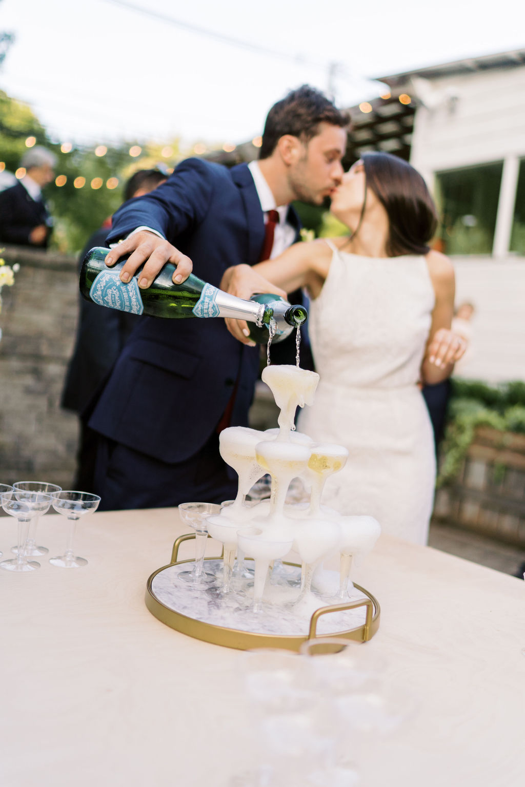 bride and groom share a kiss while pouring champagne on glass tower