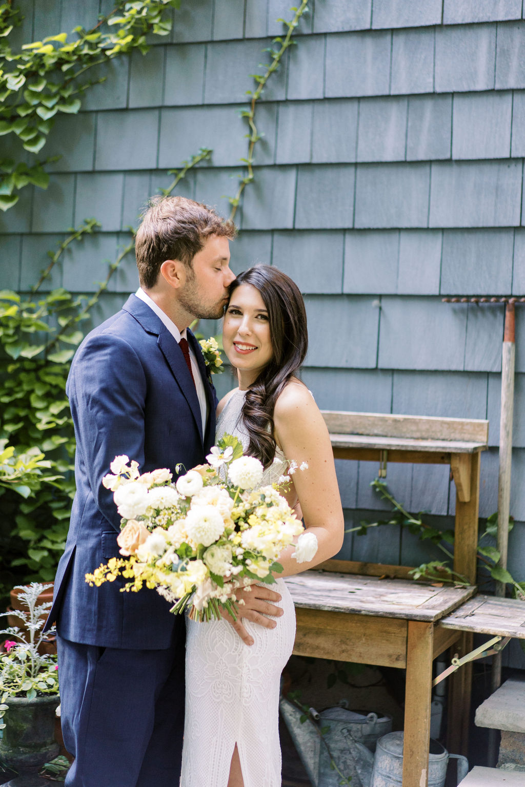 groom kisses bride while she smiles holding floral bouquet