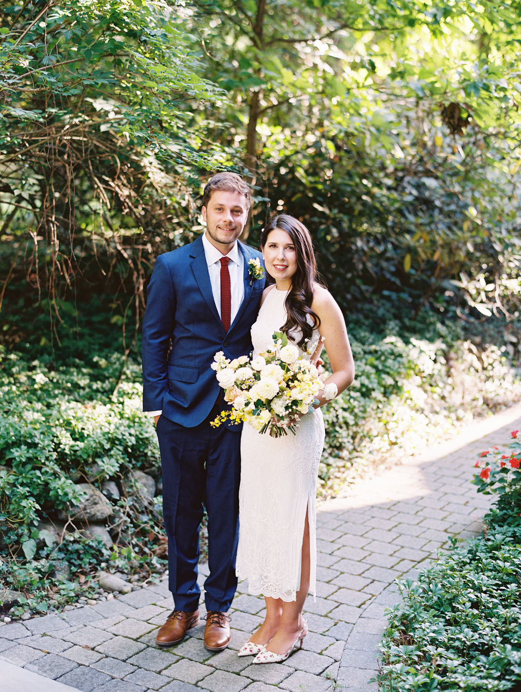 bride and groom smile on stone pathway in garden center