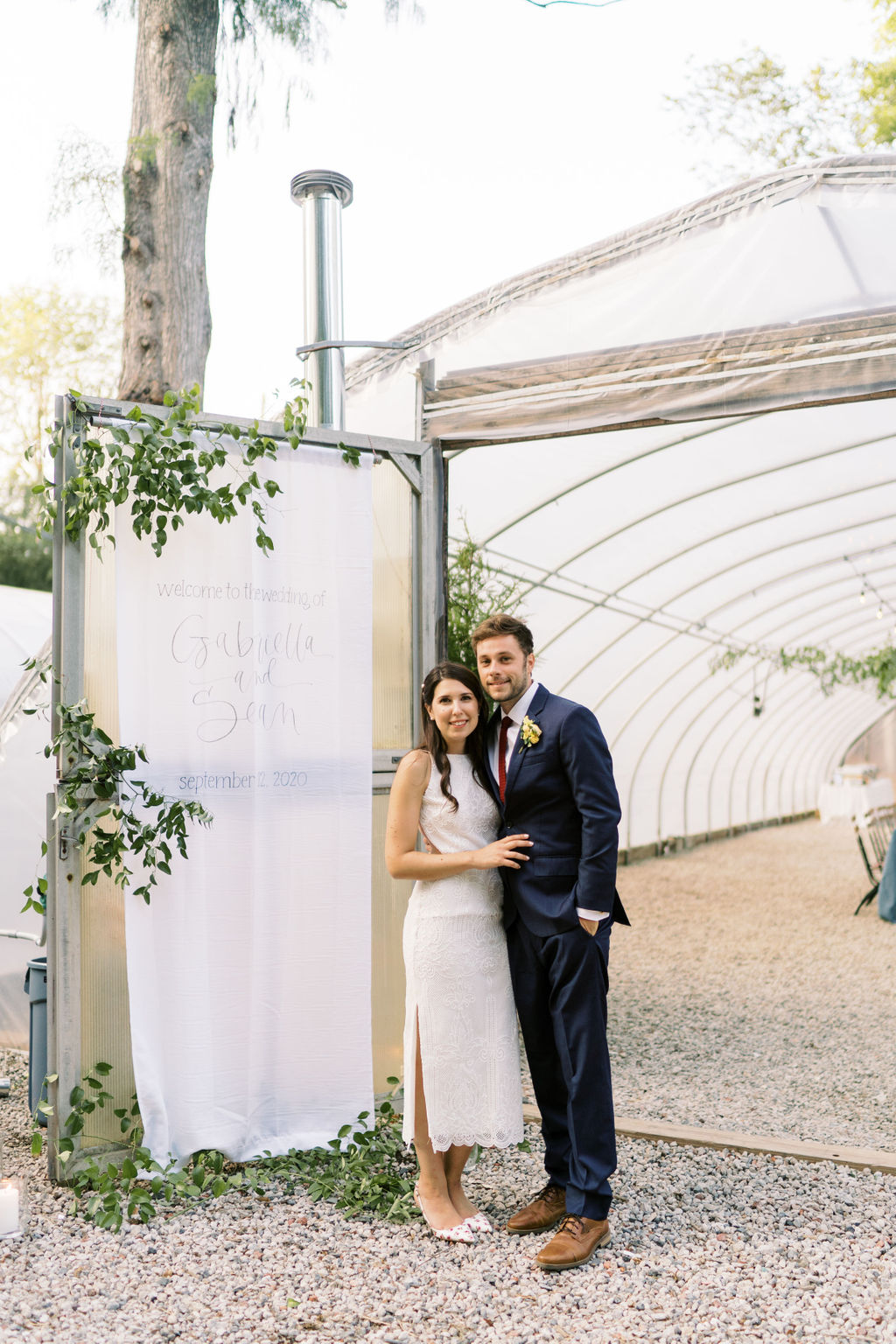 bride and groom standing outside next to wedding sign
