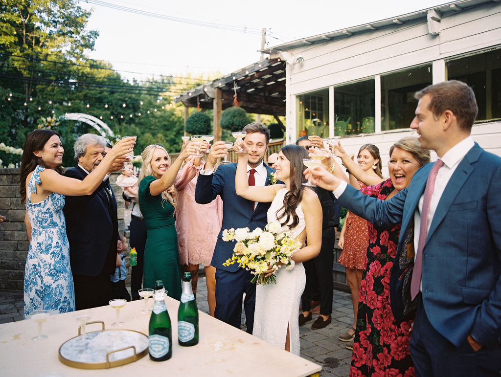 bride and groom share a toast with friends and family