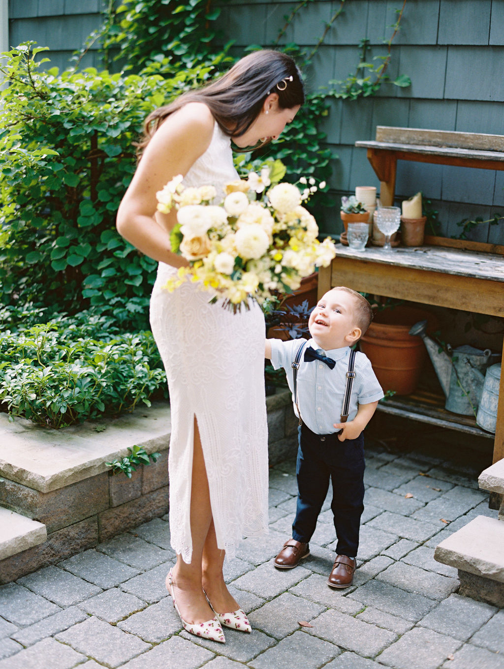 bride hold bouquet smiling down at nephew outside