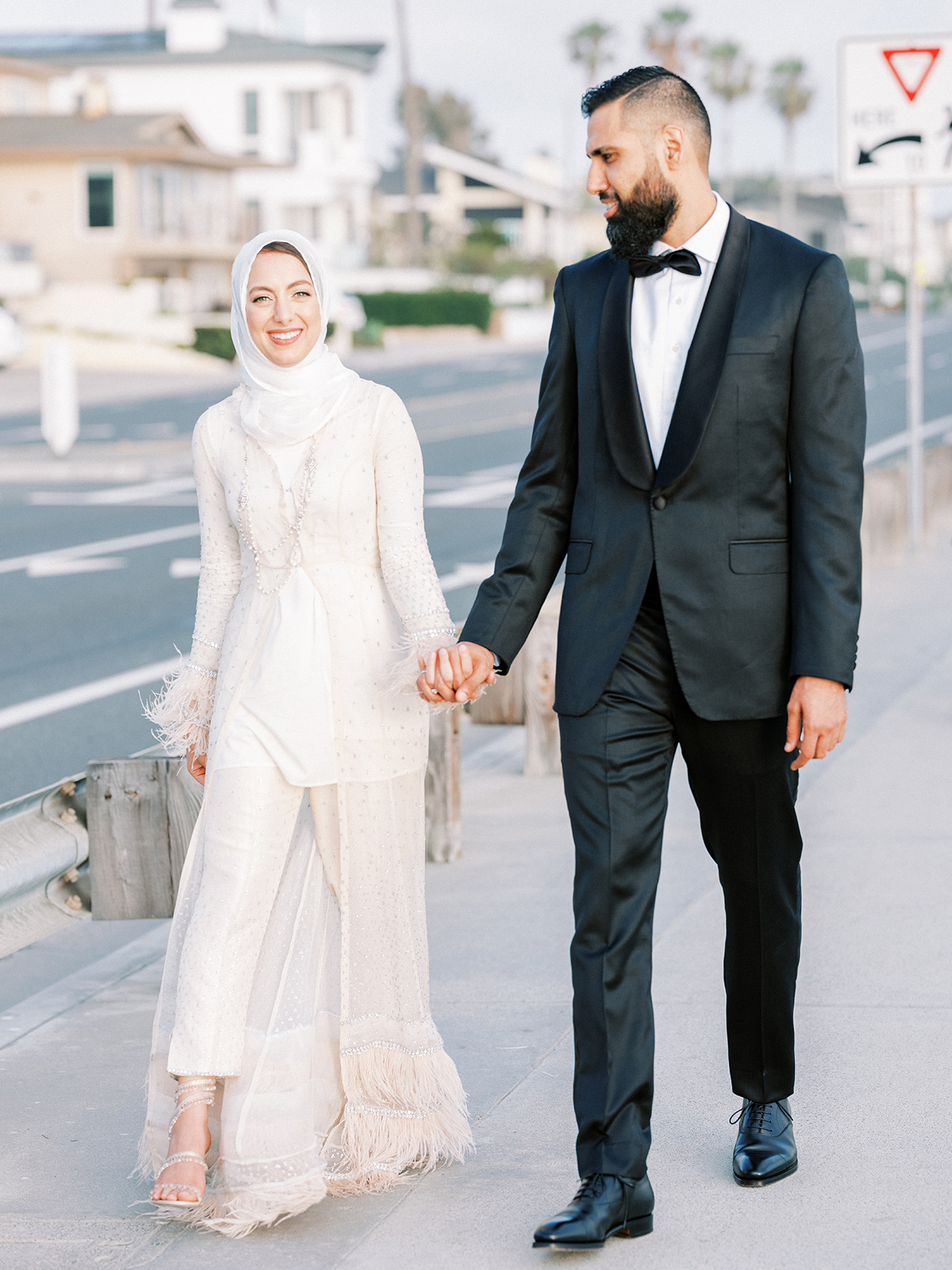 bride and groom holding hands walking along roadway