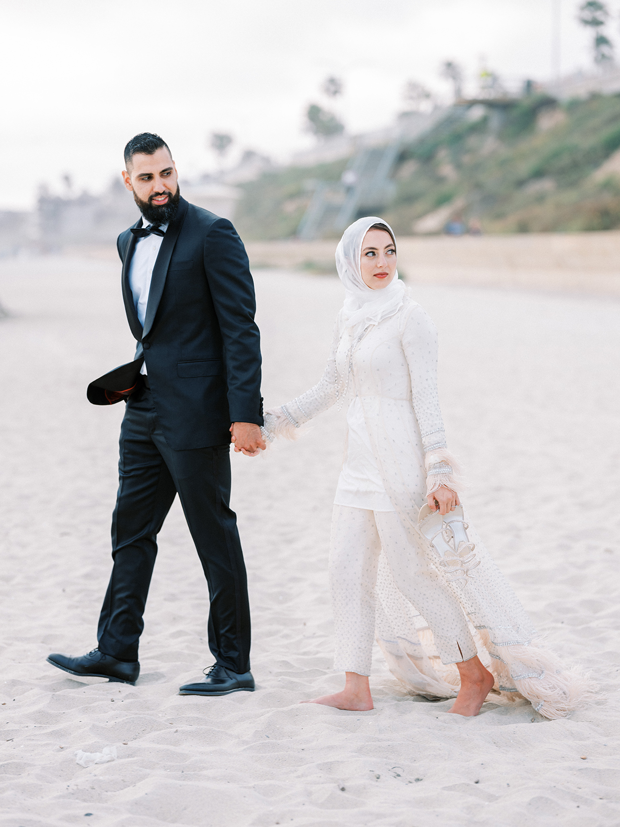 bride and groom holding hands walking on sandy beach