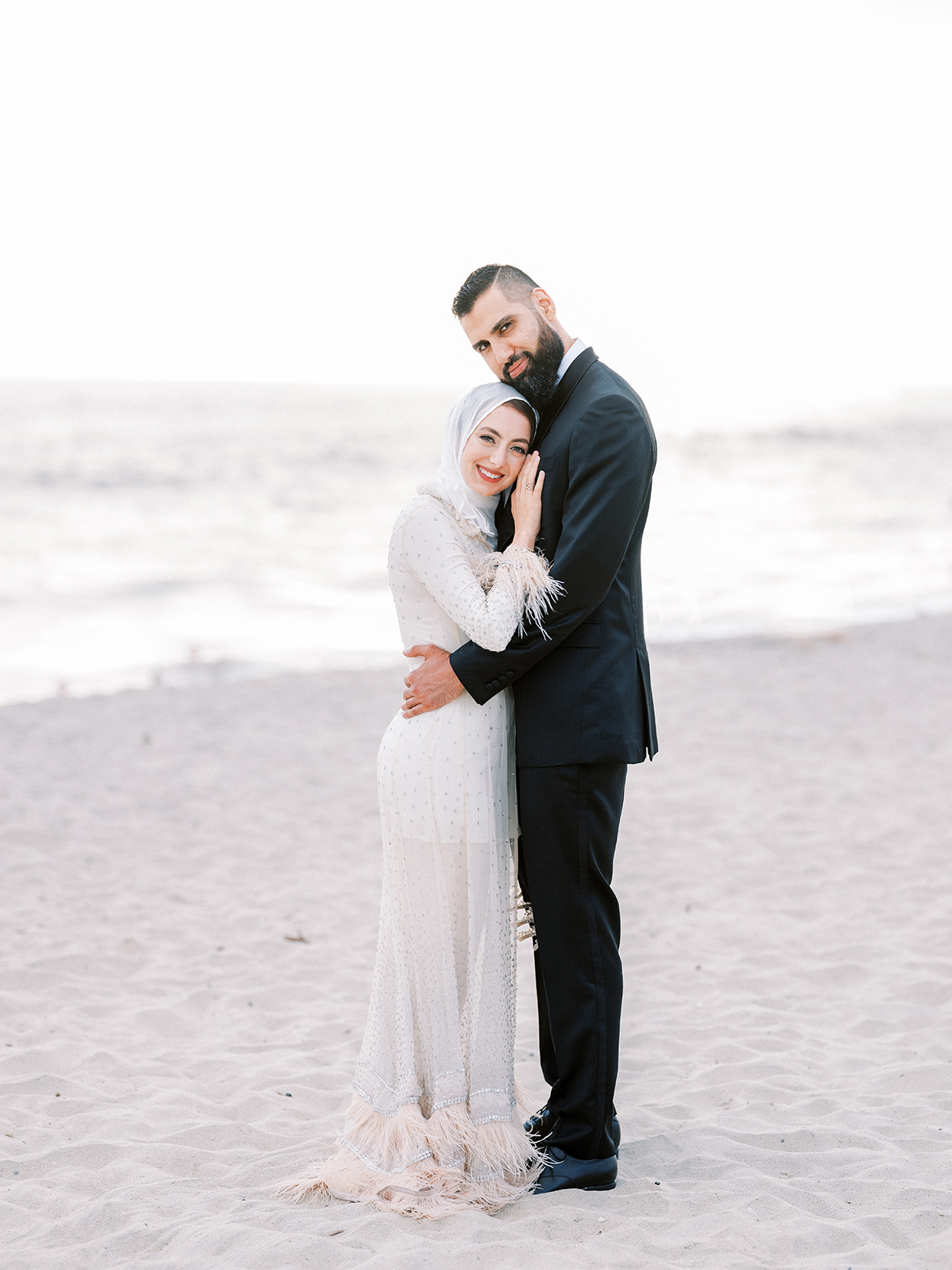 bride and groom embracing smiling on sandy beach