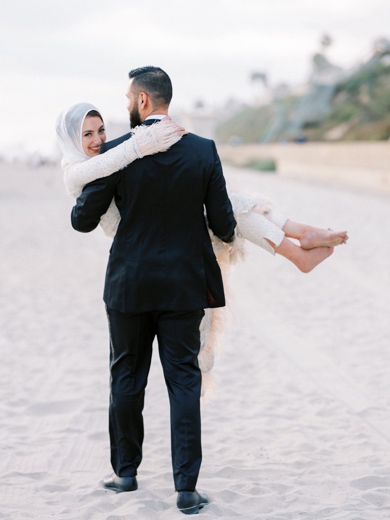 bride smiling over grooms shoulder as he carries her on the beach