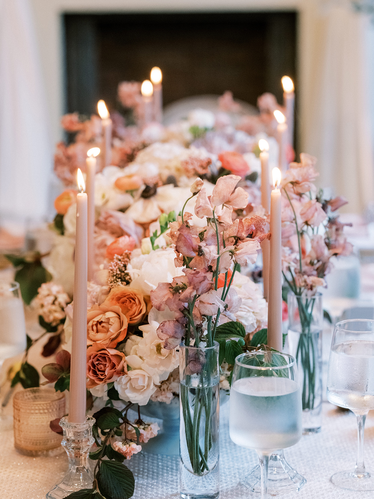 low floral wedding reception table centerpieces with lit tapper candles