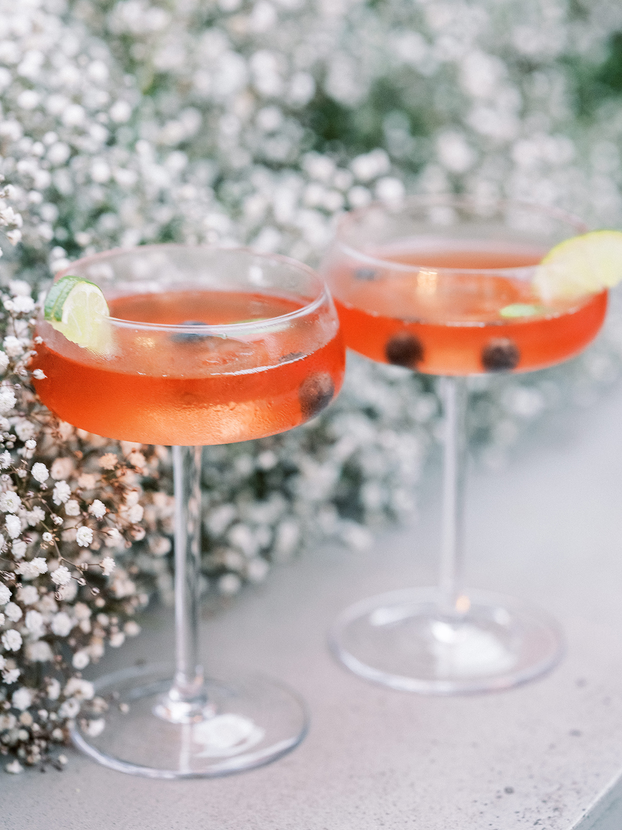 red cocktails with lime wedge on glass edge