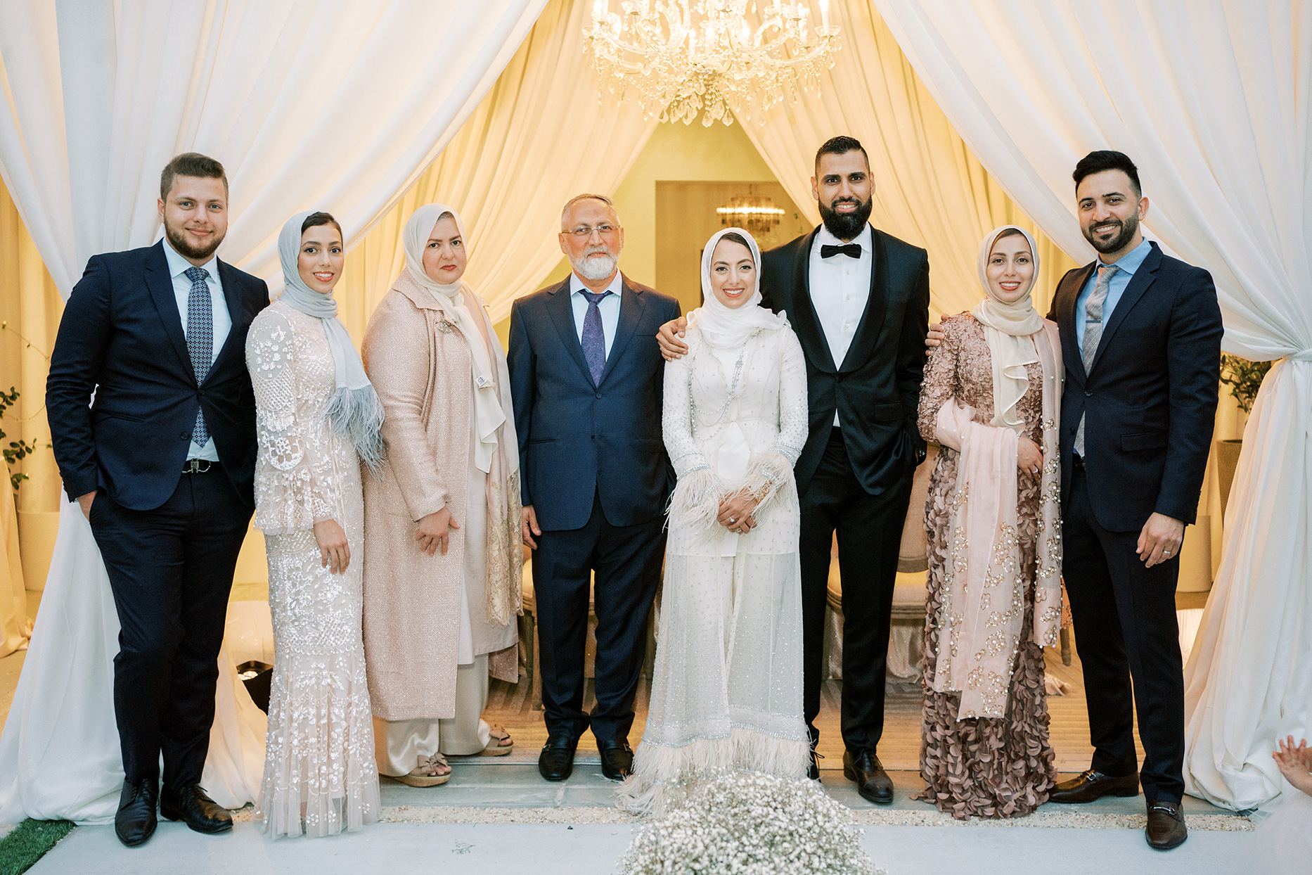 bride and groom standing with family smiling