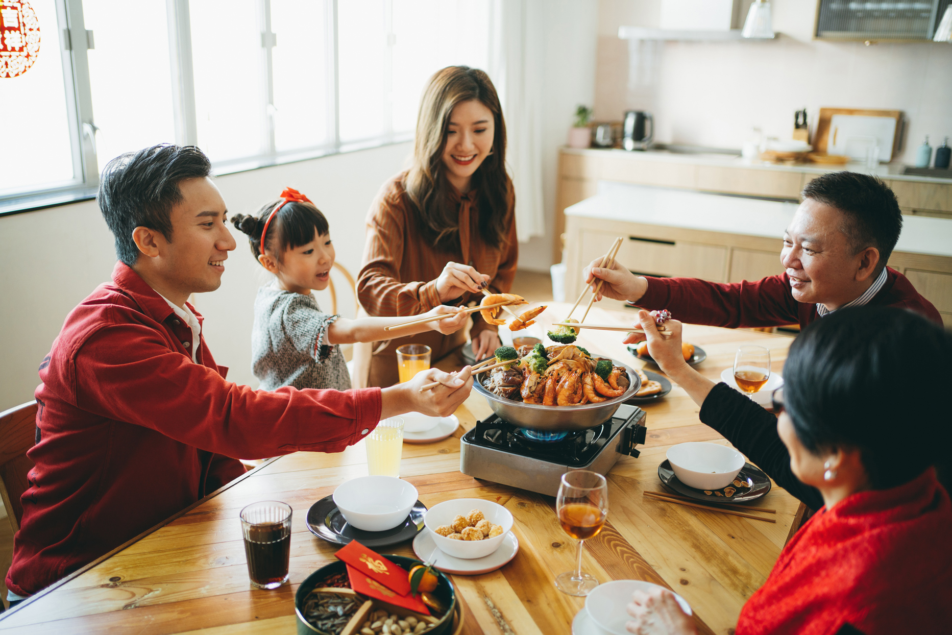 family sitting at table eating food for lunar new year