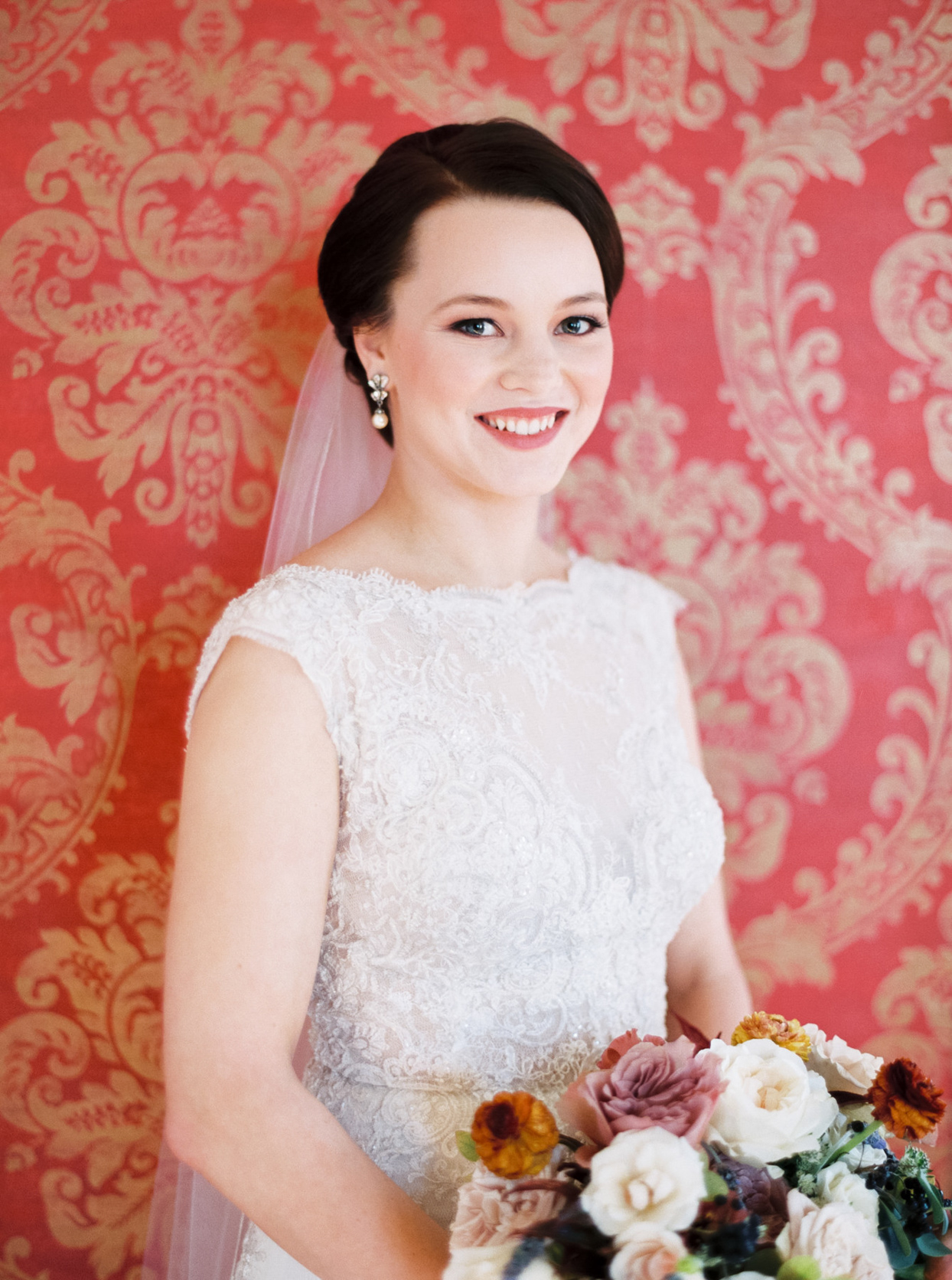 bride in white lace gown in front of patterned wall