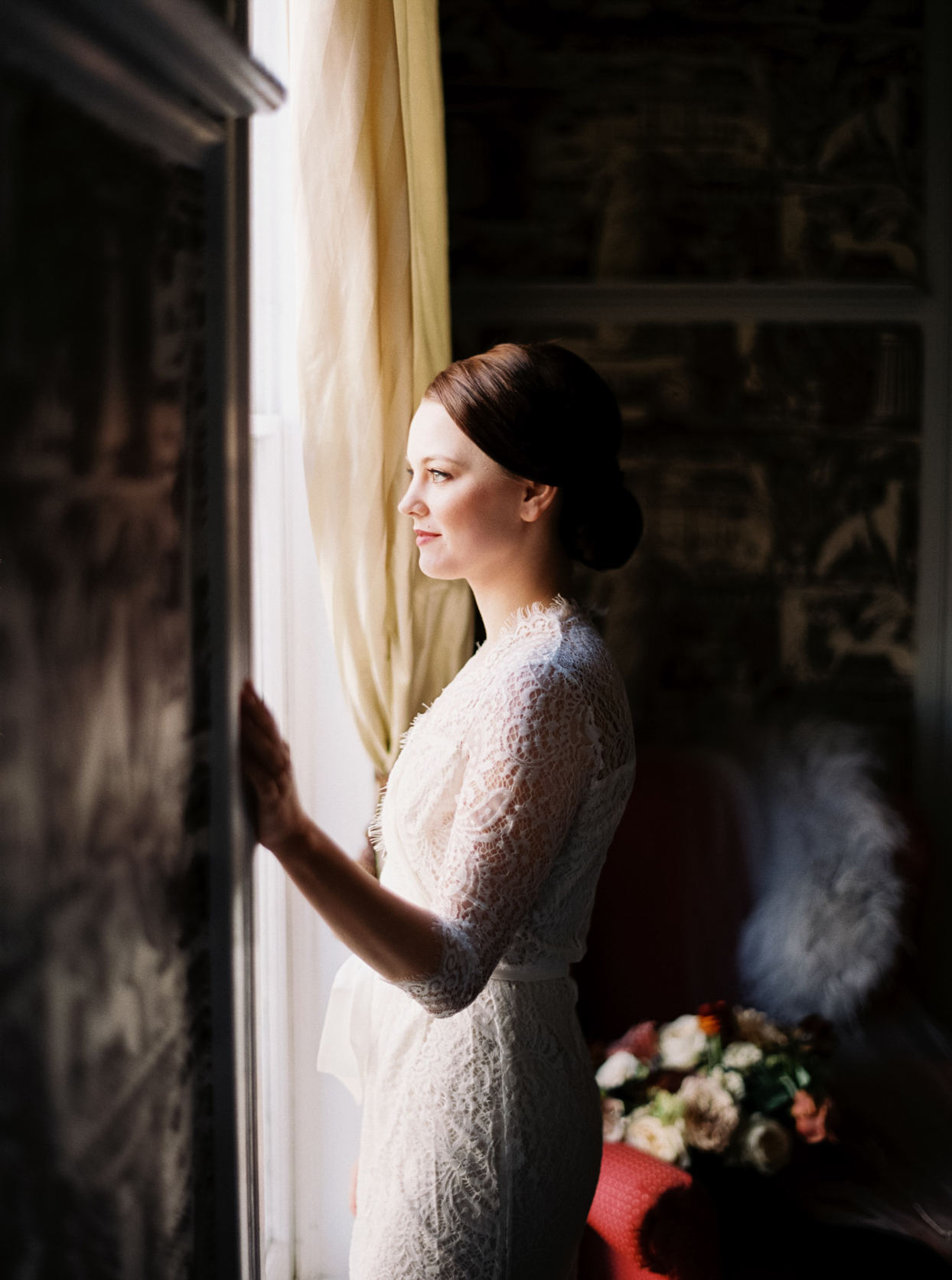 bride in lace dress looking out window
