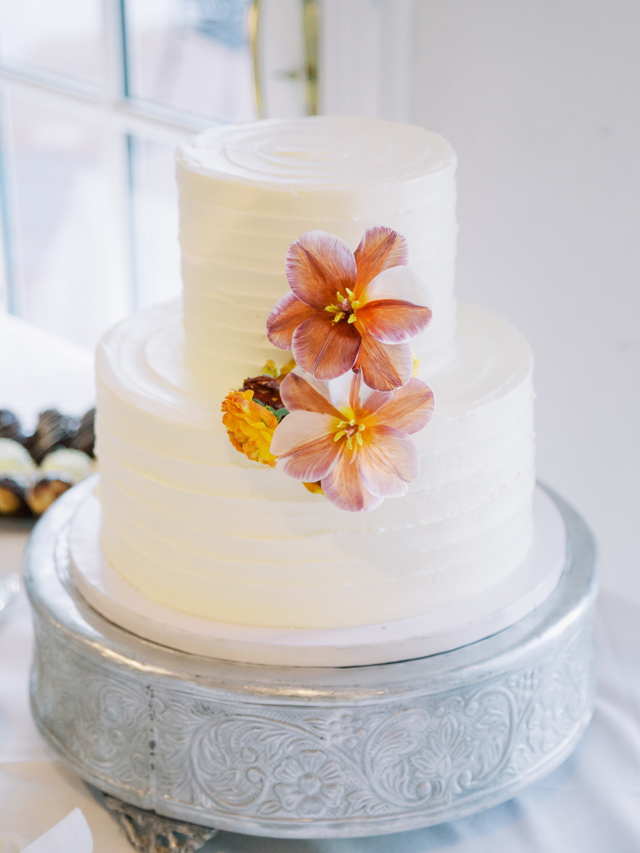 simple white wedding cake with two-tone floral decorations