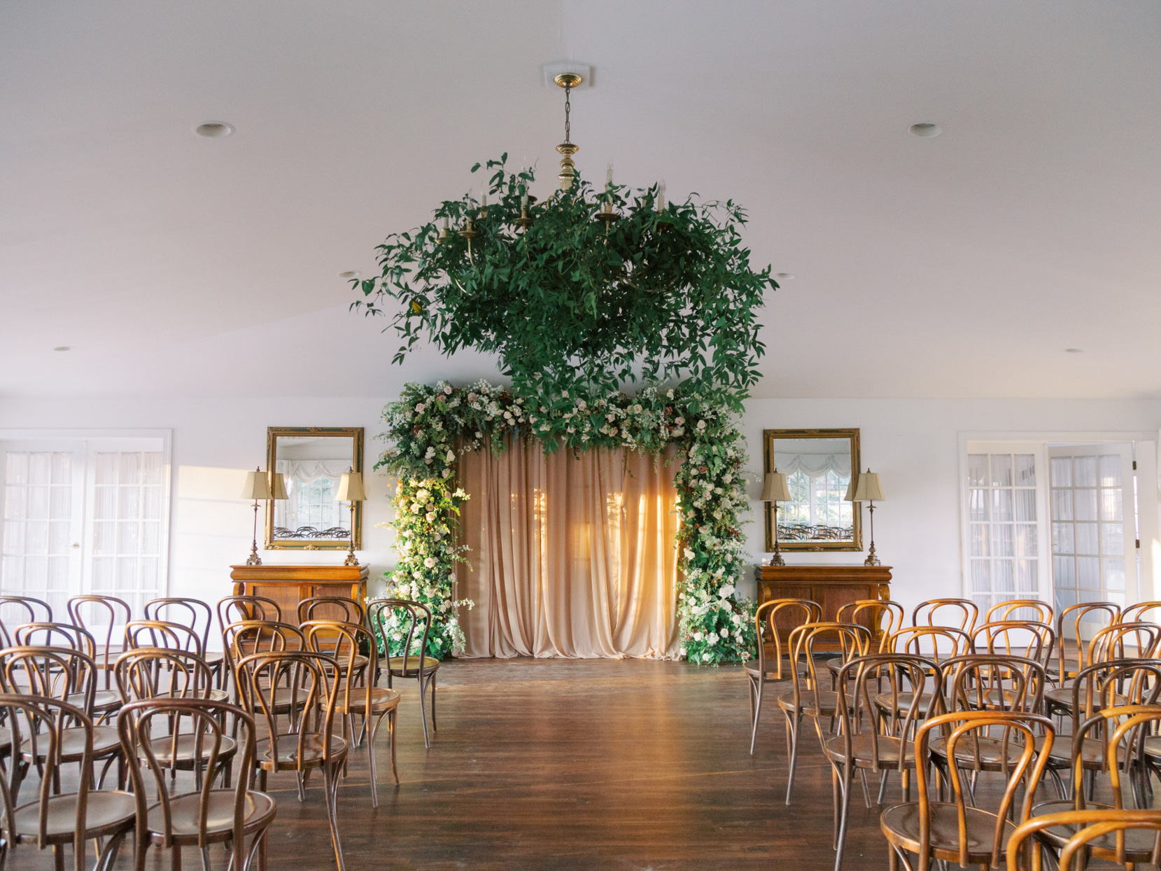 elegant indoor ceremony setting with floral arch and greenery chandelier