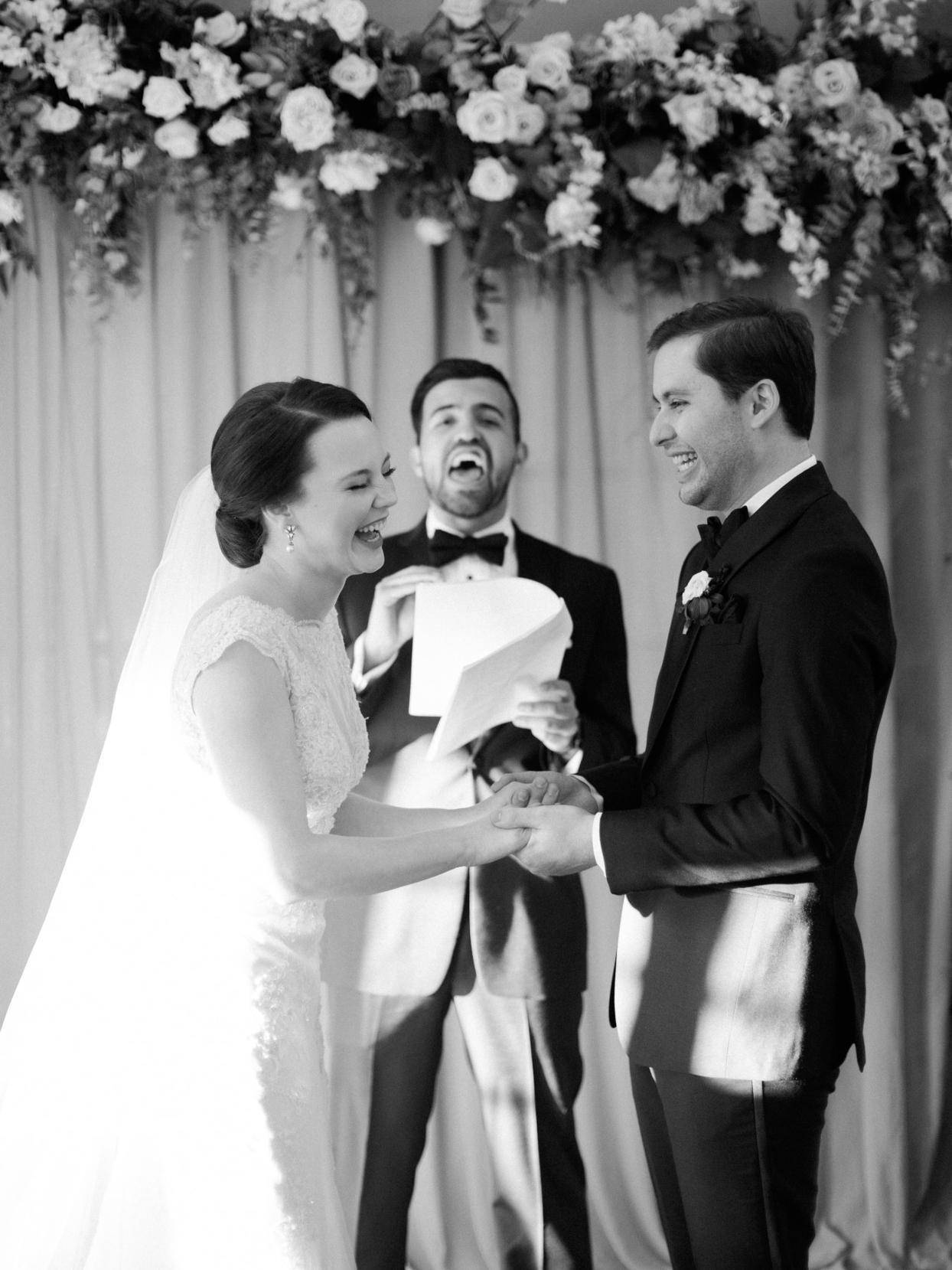 couple holding hands and laughing during wedding ceremony