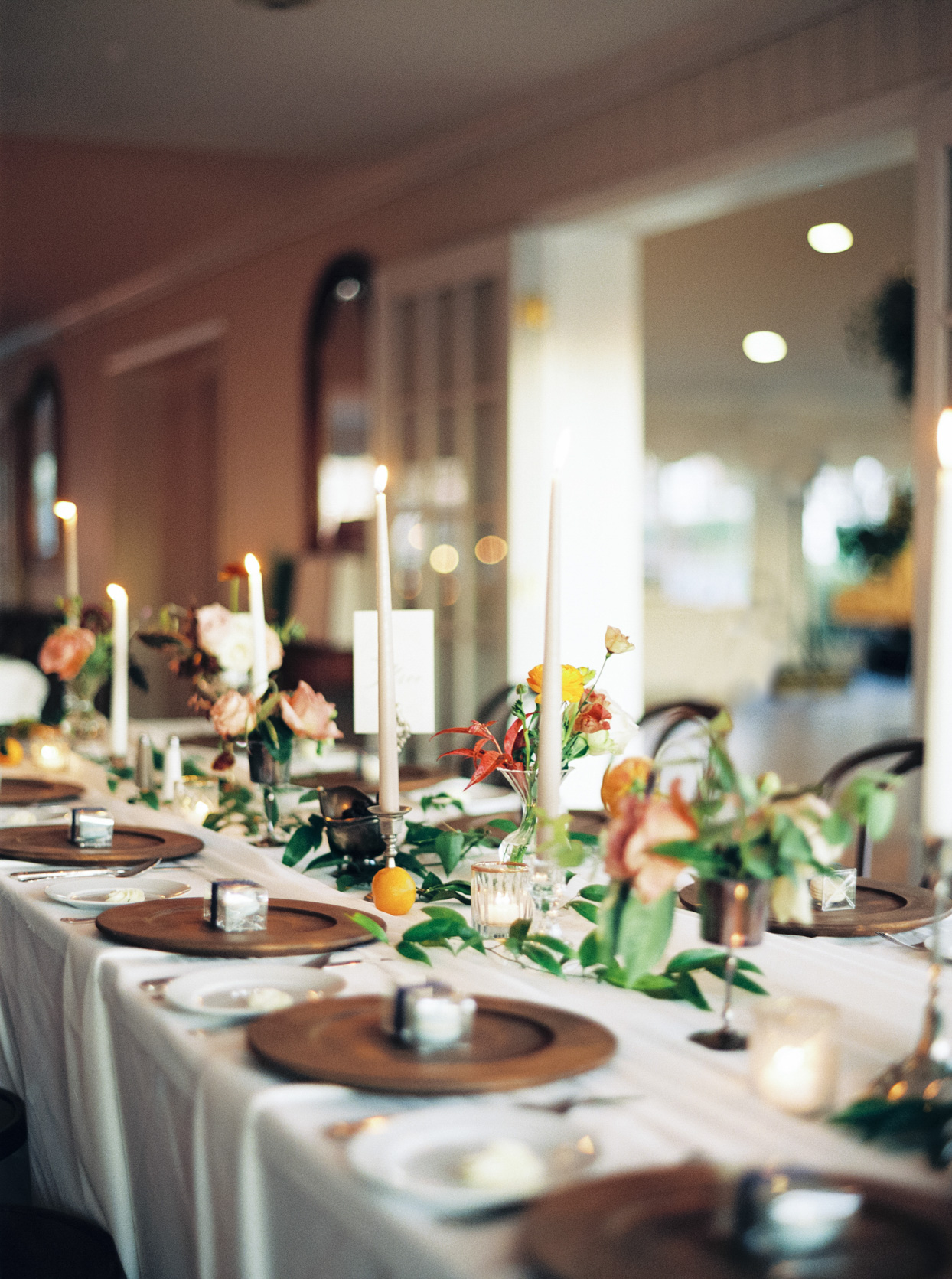elegant wedding table settings with candles, flowers, citrus, and wooden chargers