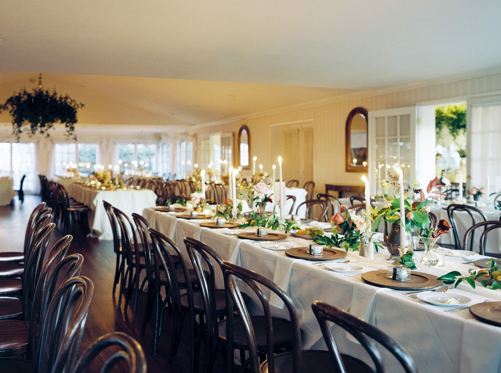 reception room with long tables with lit candles and flowers
