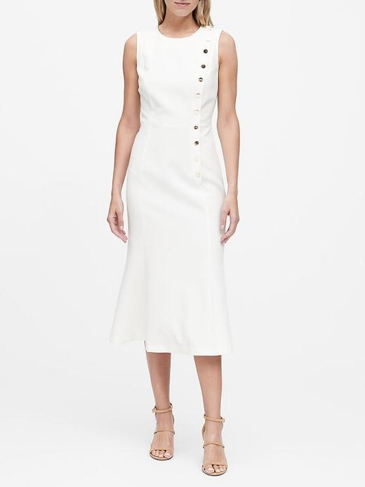 model wearing white midi-length sleeveless dress with buttons going up the side
