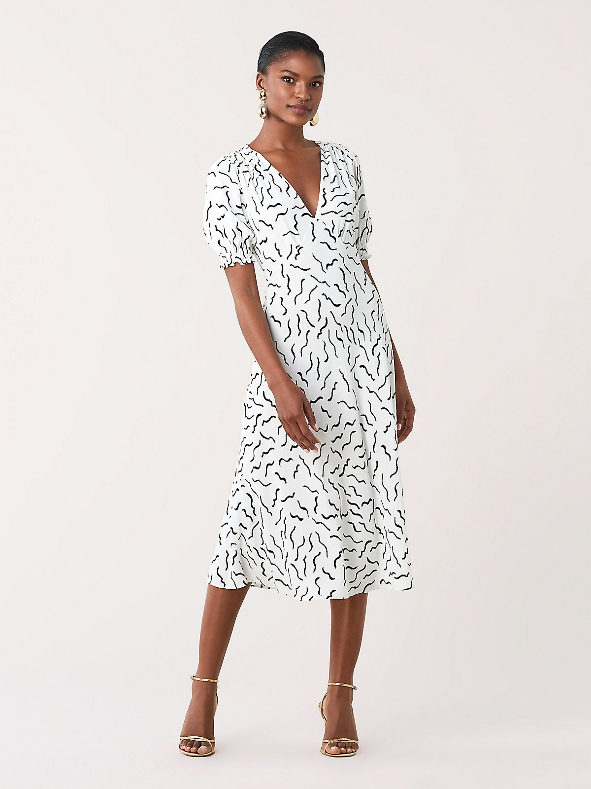 model wearing a black and white patterned midi-length dress